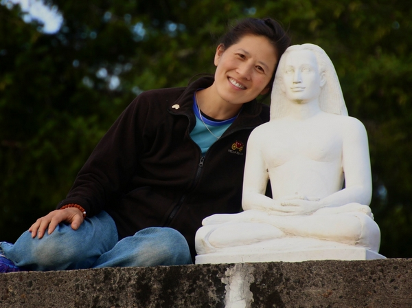 A disciple of Paramhansa Yogananda smiles and leans on a statue of Babaji